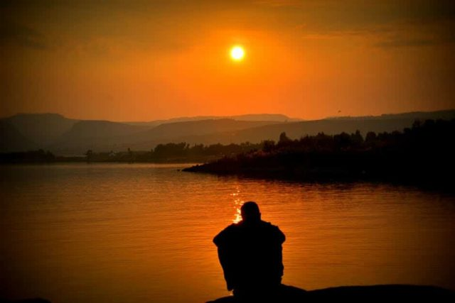 gain access to heaven knowing for sure man sitting in the sunset of a lake and mountains in the background with orange sky